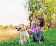 Pretty young woman with friendly golden retriever dog on the walk royalty free stock images