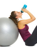 Fitness young woman sitting near fitness ball and drinking water Royalty Free Stock Photos