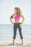 Fitness young woman standing on beach and looking on copy space Stock Photography