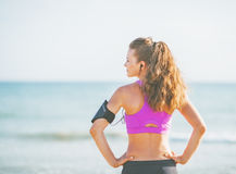 Fitness young woman standing on beach and looking on copy space Stock Images