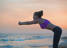 Fitness young woman stretching on beach in the evening Royalty Free Stock Photos