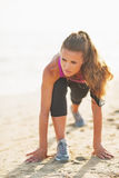 Fitness young woman stretching on beach. Fitness young woman with long hair stretching on sandy beach Royalty Free Stock Photos