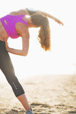 Fitness young woman stretching on beach . rear view Stock Photo