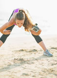 Fitness young woman stretching on beach Stock Photos