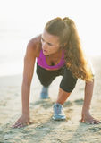 Fitness young woman stretching on beach Royalty Free Stock Image