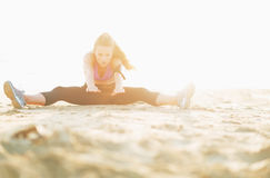 Fitness young woman stretching on beach Royalty Free Stock Images