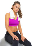 Fitness young woman with towel sitting on fitness ball Royalty Free Stock Image