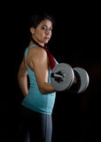 Fitness young woman in training with dumbbells on a black bakground, sporty muscular female brunette. Fitness young woman in training with dumbbells, sporty Royalty Free Stock Photo
