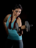 Fitness young woman in training with dumbbells on a black bakground, sporty muscular female brunette. Fitness young woman in training with dumbbells, sporty Royalty Free Stock Photography
