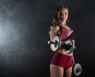 Fitness young woman in training with dumbbells, sporty muscular female brunette in smoke. Girl wearing sports clothes working out with dumbbell over white Stock Images