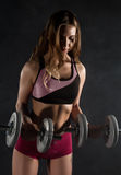 Fitness young woman in training with dumbbells, sporty muscular female brunette in smoke. Girl wearing sports clothes working out with dumbbell over white Royalty Free Stock Photography