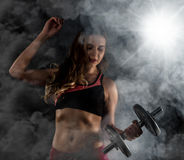 Fitness young woman in training with dumbbells, sporty muscular female brunette in smoke. Girl wearing sports clothes working out with dumbbell over white Stock Image