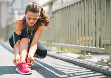 Fitness young woman tying shoelaces in the city Royalty Free Stock Photography