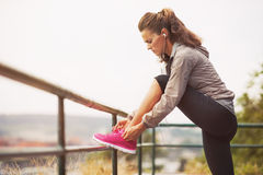 Fitness young woman tying shoelaces outdoors. Modern fitness young woman tying shoelaces outdoors Royalty Free Stock Image