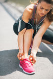 Fitness young woman tying shoelaces outdoors Stock Photos