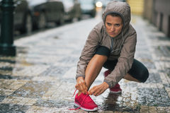 Fitness young woman tying shoelaces in rainy city Stock Image