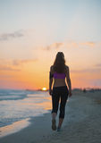 Fitness young woman walking on beach at dusk . rear view Stock Image
