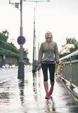 Fitness young woman walking in rainy city Royalty Free Stock Image