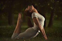 Fitness young yoga woman doing stretching exercises on grass. Royalty Free Stock Photos