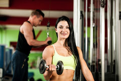 Fitness youple workout - fit mann and woman train in gym Royalty Free Stock Photography