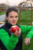 Fitnestrainer die een appel aanbieden bij openluchtgymnastiek royalty-vrije stock fotografie