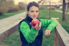 Fitnestrainer die een appel aanbieden bij openluchtgymnastiek stock afbeelding