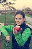 Fitnestrainer die een appel aanbieden bij openluchtgymnastiek royalty-vrije stock afbeelding