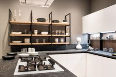 Fitted kitchen interior with gas hob and shelving. Compact fitted kitchen interior with gas hob in a marble effect counter and shelving with crockery royalty free stock photography