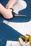 Fitter cuts out dress according with pattern. Fitter cuts out dress from blue fabric according with pattern Royalty Free Stock Photo