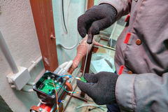 Fitter installs control devices for central heating systems, boi Royalty Free Stock Photo