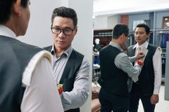 Fitting bespoke suit. Professional tailor fitting bespoke suit to his mature client stock images