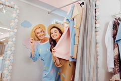 Happy mother and daughter fitting new summer dresses. Fitting dresses. Happy mother and daughter smiling broadly while fitting new summer dresses royalty free stock image