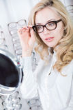 Fitting glasses at an optometry office. Beautiful blond lady is fitting eyeglasses at an optometry office Royalty Free Stock Images