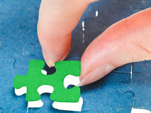 Fitting the last green piece of puzzle Stock Images