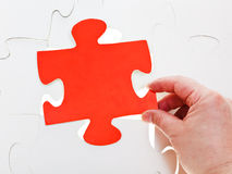 Fitting red puzzle piece on free space Stock Photo