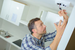 Fitting smoke alarm in home Royalty Free Stock Image