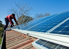 Fitting solar panels to roof. Of house Royalty Free Stock Photo