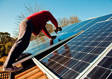 Fitting solar panels to roof of house. Workman fitting solar panels to roof of house Stock Images