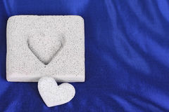 Fitting stone hearts on the blue satin Stock Photography