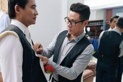 Fitting suit. Vietnamese fashion designer fitting bespoke suit to model stock photo
