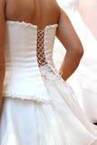 Fitting of wedding dress. Woman puts on beautiful white wedding dress Stock Images