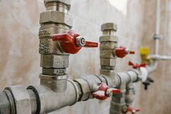Free Fittings And Valve, Pipes And Adapters. Plumbing Fixtures And Piping Parts. Focus On The Red Crane Stock Photography - 182143862