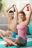 Fittness at home. Young couple doing dumbbell exercise sitting on fittness mat at home, smiling Royalty Free Stock Photo