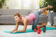Fittness at home. Young woman doing leg exercises lying on fitness mat in living room, smiling Royalty Free Stock Image