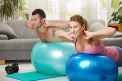 Fittness at home. Young couple doing fit ball exercises in living room, smiling Royalty Free Stock Photos