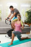 Fittness at home. Man training on exercise bike, woman doing streching exercise on fitness mat at home Stock Photo