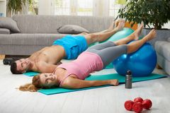 Fittness at home. Young couple doing abdominal exercise with fit ball in living room, smiling Stock Photos