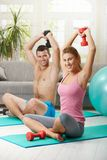 Fittness at home. Young couple doing dumbbell exercise sitting on fittness mat at home, smiling Stock Photos