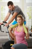 Fittness at home. Man training on exercise bike, woman doing streching exercise on fitness mat at home Royalty Free Stock Images
