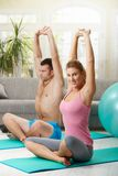 Fittness at home. Young couple sitting at fitness mattress and streching before exercises Royalty Free Stock Photography